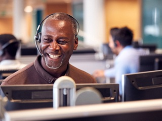 person smiling and wearing a call headset