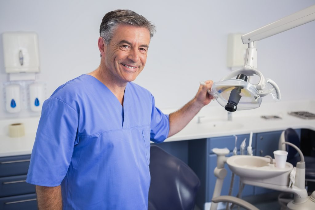 Smiling dentist with light