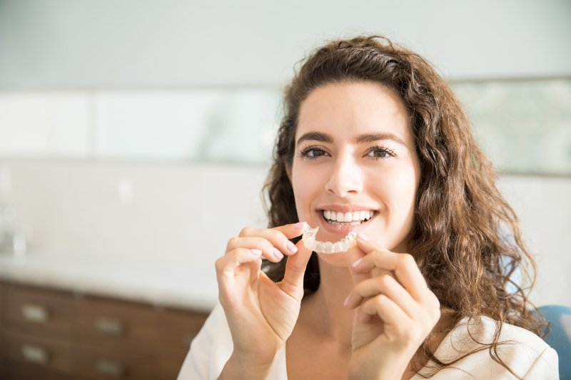 a young woman prepares to insert a clear retainer after Invisalign treatment