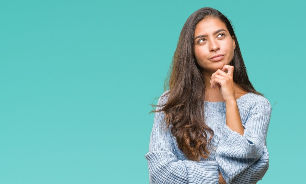 Woman in blue sweater wondering about Invisalign after braces