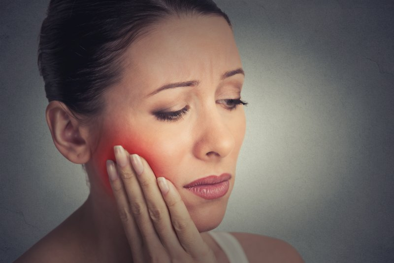 woman holds cheek in pain